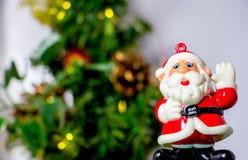 站立近的圣诞树1的圣诞老人五颜六色的小雕象 库存照片