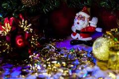站立近的圣诞树2的圣诞老人五颜六色的小雕象 免版税库存图片
