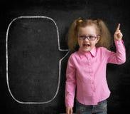 站立近的学校黑板的镜片的滑稽的孩子 免版税图库摄影