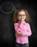 站立近的学校黑板的镜片的滑稽的孩子 免版税库存照片