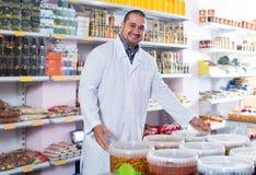 站立近的容器用在调味的bri的橄榄的商店职员 库存图片