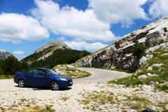 站立近的山路的蓝色汽车 免版税图库摄影