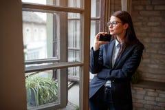 站立近的开窗口的妇女在办公室 免版税图库摄影