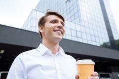 站立近的摩天大楼和喝咖啡的愉快的商人 图库摄影