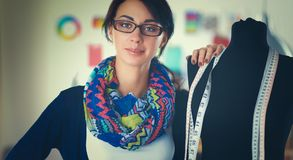 站立近的时装模特的微笑的时装设计师在办公室 库存图片