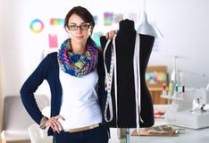 站立近的时装模特的微笑的时装设计师在办公室 免版税库存照片