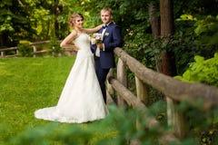 站立近的树篱的夫妇在森林里 免版税库存图片