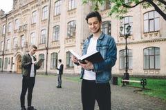 站立近的校园或大学的成功的愉快的学生外面 免版税库存照片