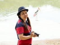 站立近的池塘的旅游妇女画象  免版税库存图片