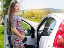 站立近的汽车的愉快的孕妇 库存图片