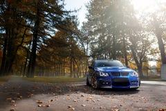 站立近的秋天的蓝色汽车BMW 3系列E91停放森林 库存图片