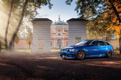 站立近的秋天的蓝色汽车BMW 3系列E91停放森林 库存照片