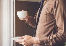 站立近的窗口和拿着咖啡杯的商人放松,当工作时 库存照片