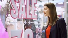站立近的窗口商店的美丽的可爱的少妇 桃红色销售额黄色 女性看的窗口商店 股票录像