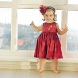 站立近的窗口的深红礼服的可爱的矮小的女婴 免版税库存照片