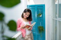 站立近的窗口的年轻俏丽的妇女读书享用  免版税库存图片