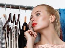 站立近的衣橱机架的美丽的白肤金发的妇女 库存图片