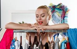 站立近的衣橱机架的美丽的白肤金发的妇女 免版税库存照片