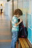 站立近的衣物柜的小男小学生在学校走廊 库存图片