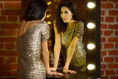 站立近的镜子与的年轻美丽的性感的妇女画象  免版税库存照片