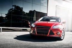 站立近的镜子修造的红色汽车 库存图片