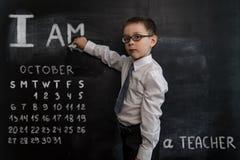 站立近的黑板的年轻男孩` s 新教师 2019日历的创造性的设计观念 10月 免版税图库摄影