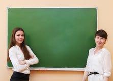 站立近的黑板的学生女孩 免版税图库摄影