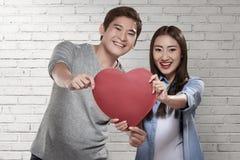 站立逗人喜爱的亚洲的夫妇拿着红色心脏 库存图片