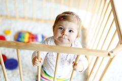 站立里面幼儿围栏的美丽的矮小的女婴 使用与五颜六色的玩具的逗人喜爱的可爱的孩子 免版税库存照片
