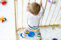 站立里面幼儿围栏的美丽的矮小的女婴 使用与五颜六色的玩具的逗人喜爱的可爱的孩子 免版税库存图片