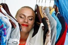 站立里面衣橱机架ful的美丽的微笑的白肤金发的妇女 免版税库存图片