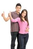 站立靠近和给赞许的一对年轻愉快的夫妇 免版税库存照片