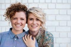 站立靠近外部的微笑的年轻女同性恋的夫妇 免版税库存照片