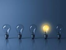 站立从在深蓝背景的未点燃的白炽电灯泡的一个黄色发光的电灯泡 免版税图库摄影