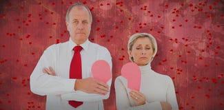 站立更旧的夫妇的综合图象拿着被伤的桃红色心 库存照片