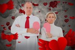 站立更旧的夫妇的综合图象拿着被伤的桃红色心 免版税图库摄影