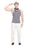 站立年轻男性的水手平直和向致敬 免版税图库摄影