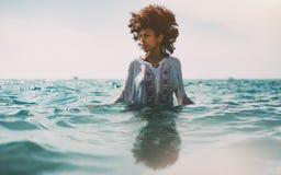 站立Briacial的女孩腰部深在海水 免版税图库摄影