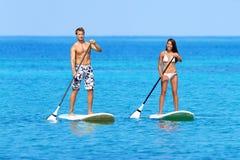 站立paddleboard明轮轮叶的海滩人 免版税库存图片