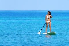 站立paddleboarding明轮轮叶的妇女 免版税库存照片