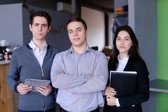 站立w的三名确信的男孩和女学生或者雇员 免版税库存图片