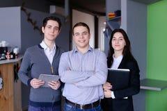 站立w的三名确信的男孩和女学生或者雇员 免版税库存照片