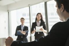 站起来和当前在业务会议期间的两名女实业家作为商人手表 免版税库存图片