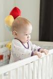 站起来在child的一个轻便小床的逗人喜爱的严肃的婴孩 免版税库存照片