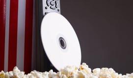 站起来用玉米花说谎, dvd圆盘和遥控倾斜的特写镜头红色白色镶边容器在箱子 免版税库存照片