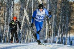 竞争人滑雪者在桦树森林里赛跑经典样式在冬天 库存照片