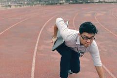 竞争企业概念 与批转的膝上型计算机准备好奔跑的确信的年轻亚洲商人在赛马跑道 免版税库存照片