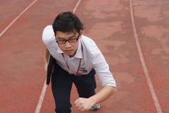 竞争企业概念 与批转的膝上型计算机准备好奔跑的确信的年轻亚洲商人在赛马跑道 免版税库存图片