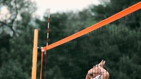 竞争在一次专业沙滩排球比赛的妇女 在2名妇女期间,防御者试图停止射击 股票视频