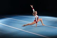 竞争在体育场内的年轻体操运动员 免版税图库摄影